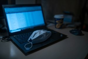 Photo of surgical face mask and a laptop computer.